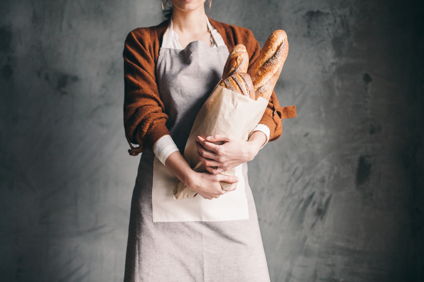 Woman Holding a Bag With Bread